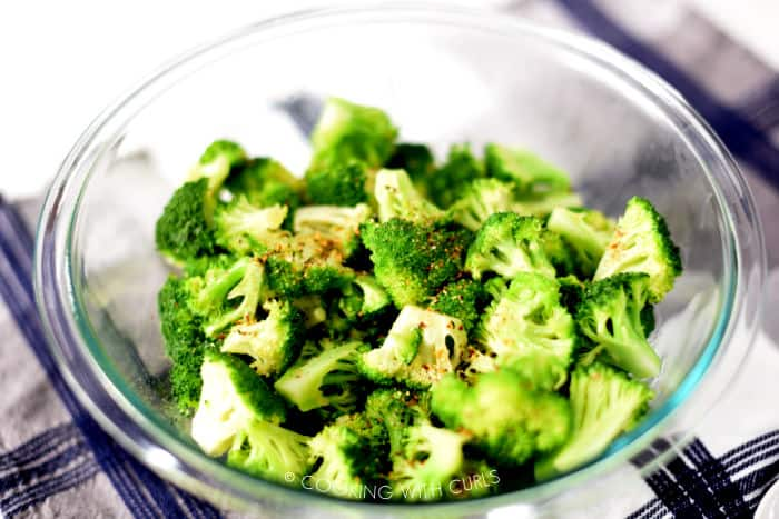 steamed broccoli in a clear glass bowl tossed with butter and garlic pepper seasoning.