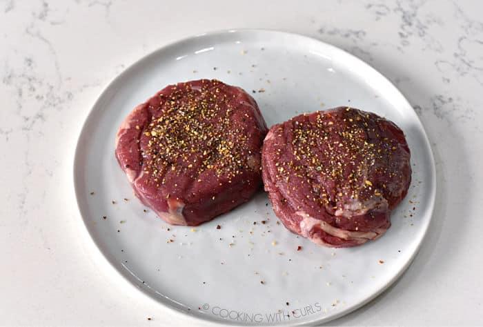 two seasoned beef tenderloin filets on a white plate.