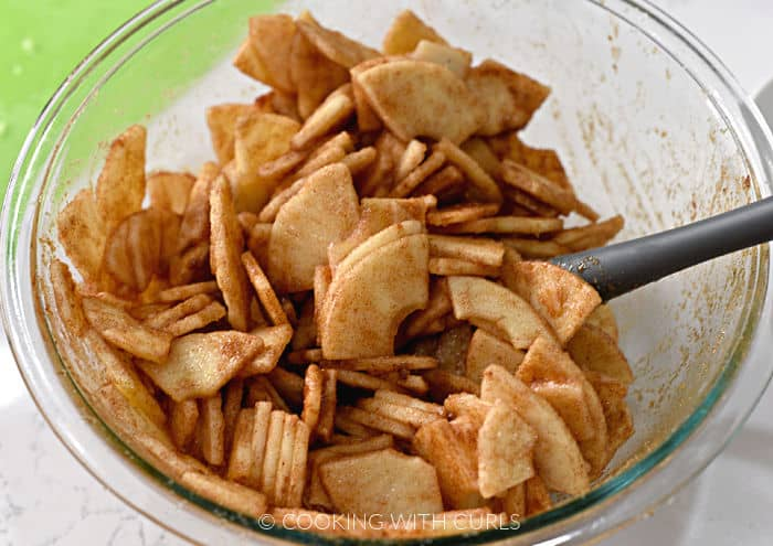 Apple slices tossed with cinnamon and nutmeg in a clear glass bowl with a gray spatula.