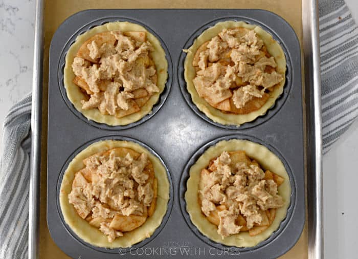 Four pie crusts filled with sliced apples and topped with streusel topping in a mini pie pan sitting on a parchment lined baking sheet.