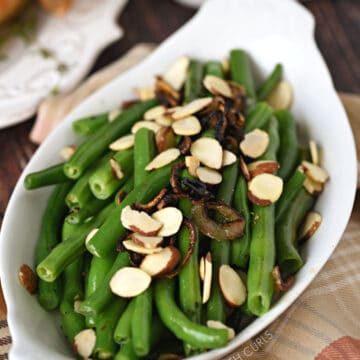 Fresh Green Beans with Caramelized Shallots and Almonds in a white au gratin dish.
