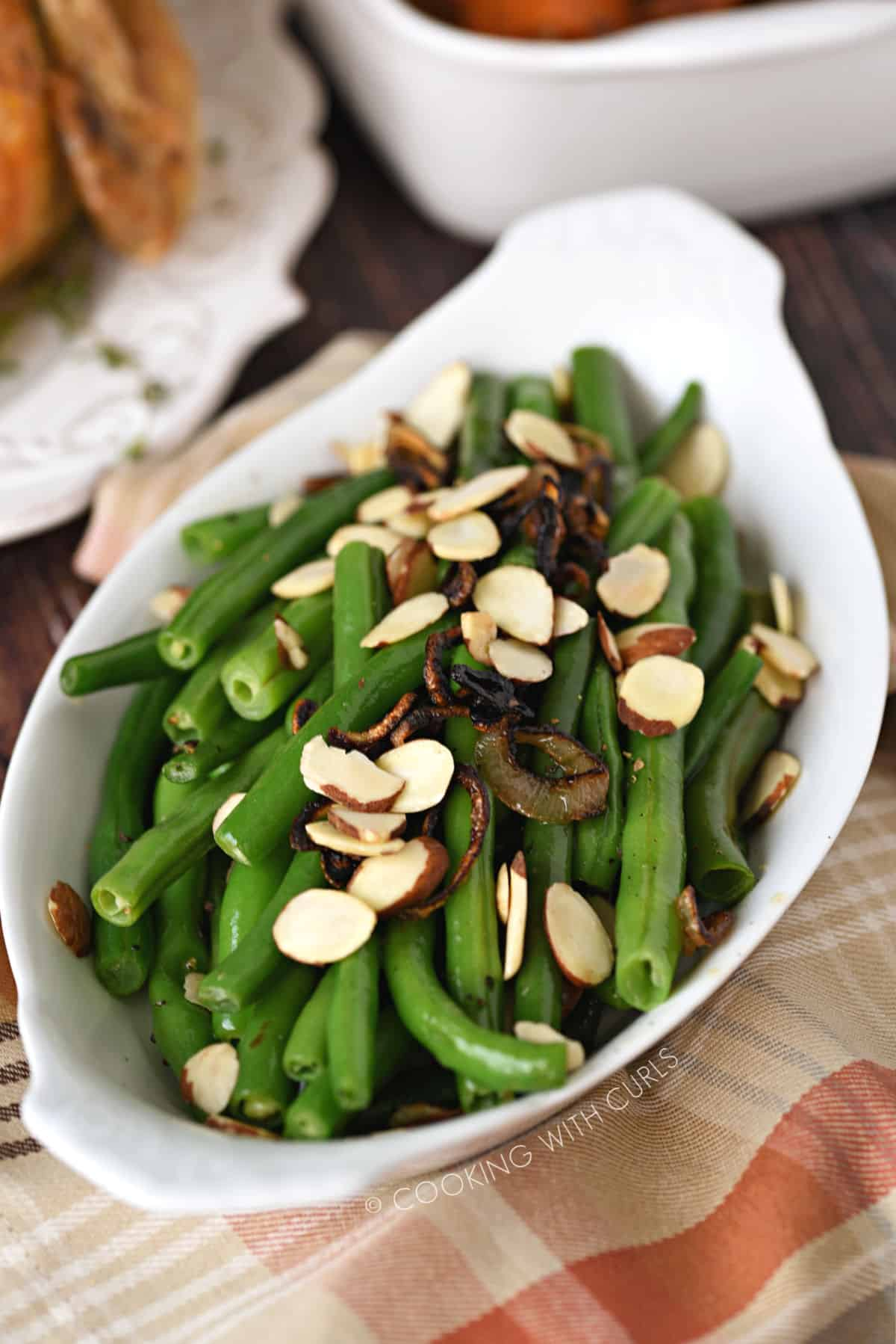 Fresh Green Beans with Caramelized Shallots and Almonds in a white au gratin dish sitting on a tan, orange and white plaid napkin.