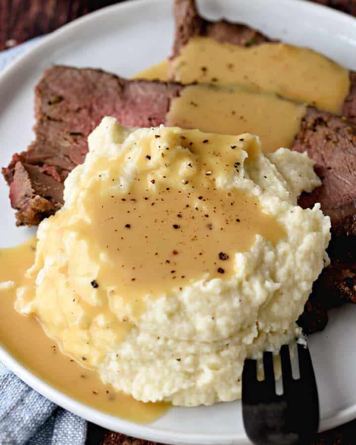 a close-up image of sliced roast beef and mashed cauliflower on a plate, topped with beef gravy and black pepper.
