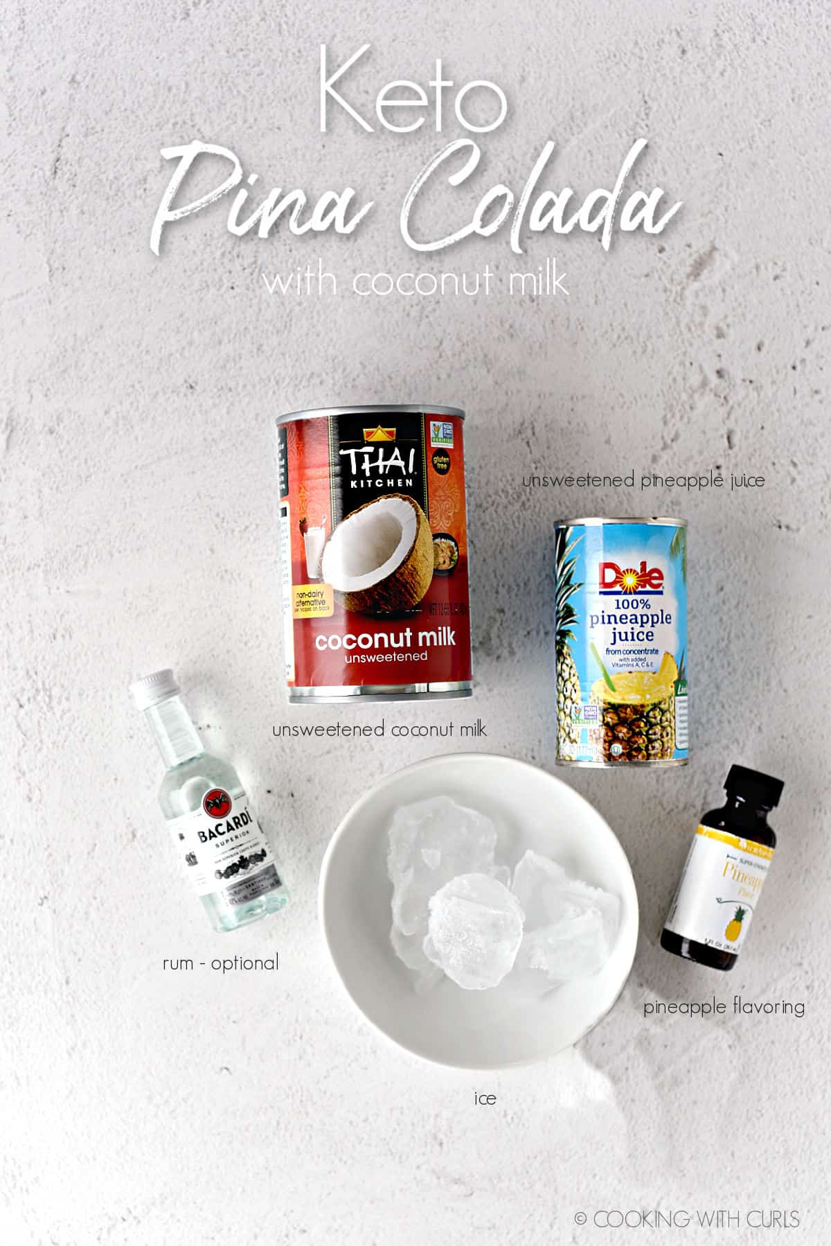 Keto Pina Colada ingredients; canned coconut milk, canned pineapple juice, tiny bottle of Bacardi rum, a white bowl with ice cubes and a bottle of pineapple flavoring.