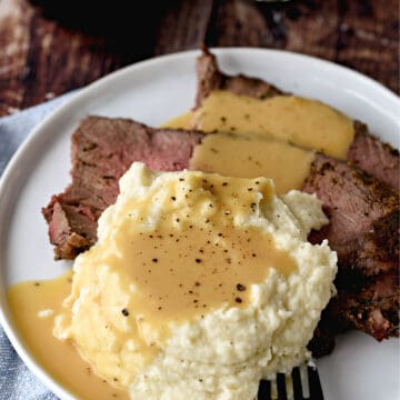 a small white plate topped with slices of roast beef, mashed cauliflower and beef gravy.