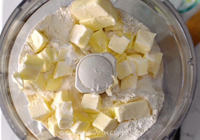 Looking down on flour, sugar and butter cubes in a food processor.