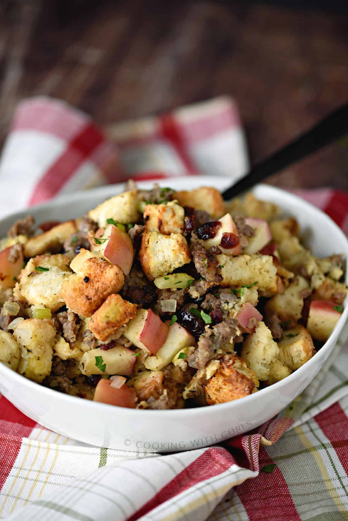 sausage apple and cranberry stuffing studded with celery and onion in a large white bowl, sitting on a red plaid napkin.