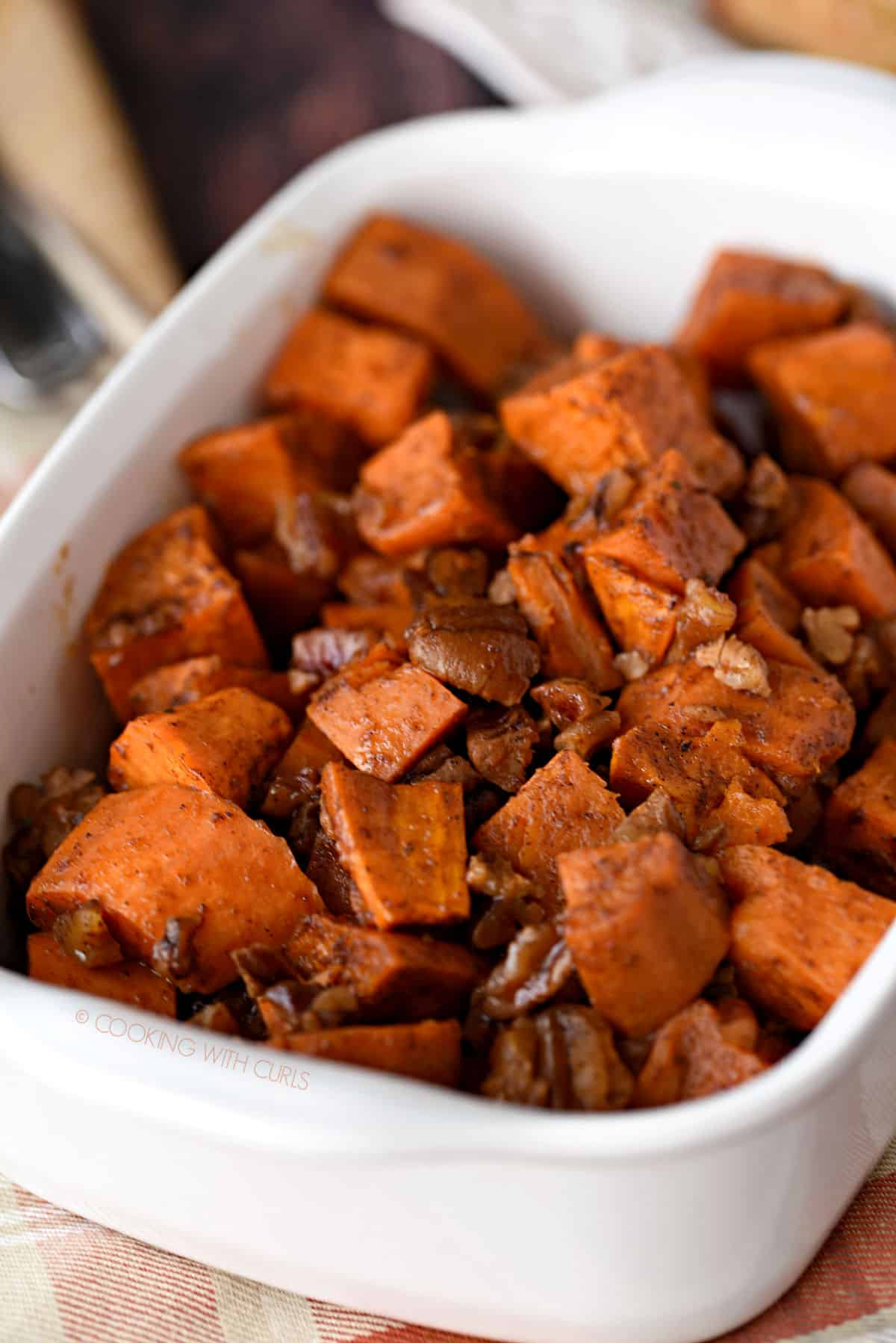 yam cubes, spices and pecans baked in a small white baking dish.