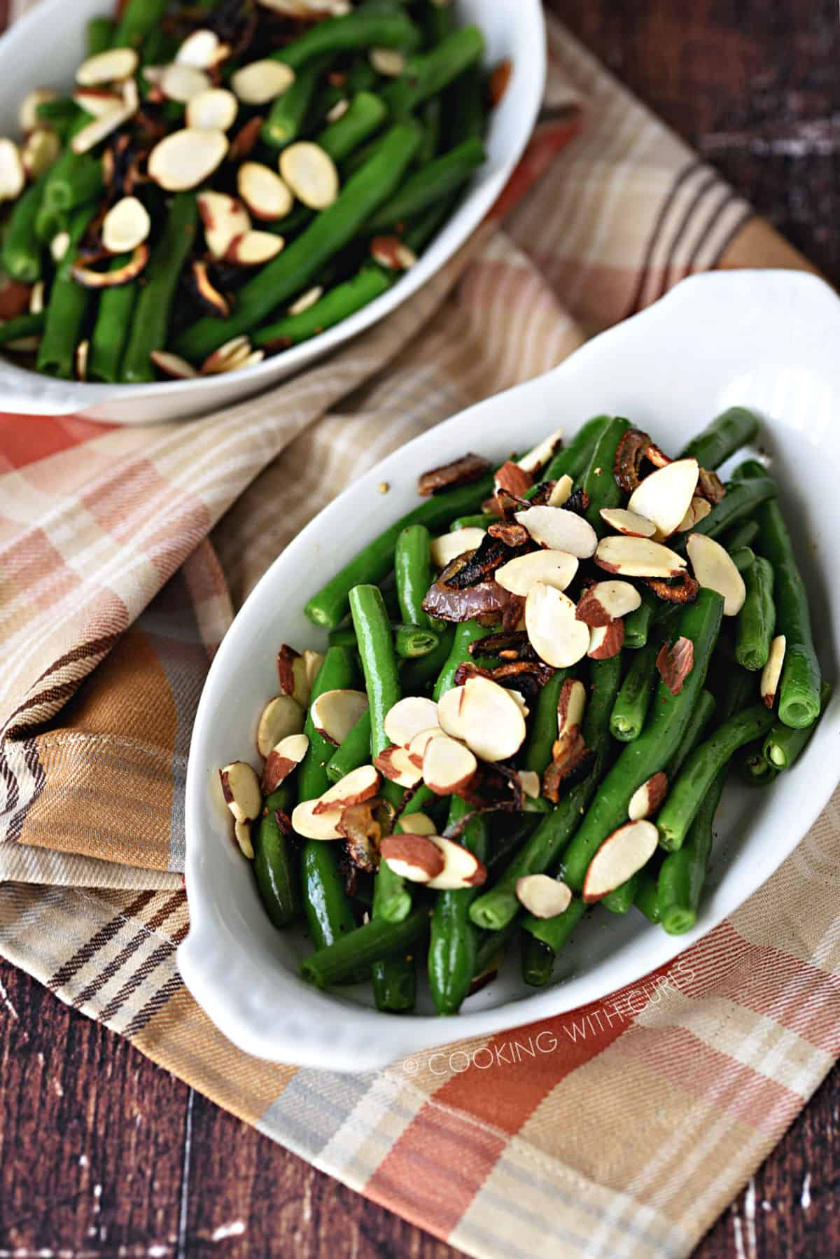 two white au gratin dishes sitting on a fall plaid napkin with green beans, shallots and sliced almonds on top.