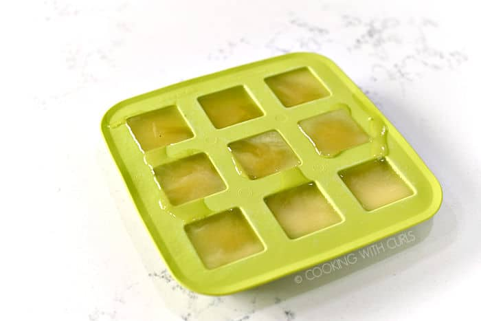 a green silicone ice cube tray filled with six square sections of frozen pineapple juice.