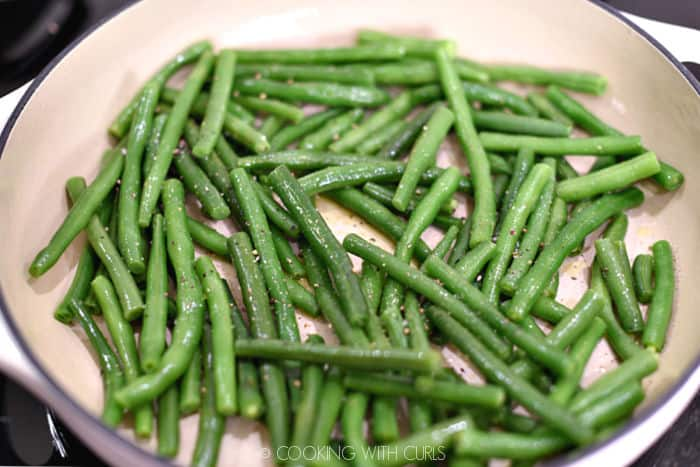 blanched green beans in a skillet with butter, oil, pepper, thyme and salt.