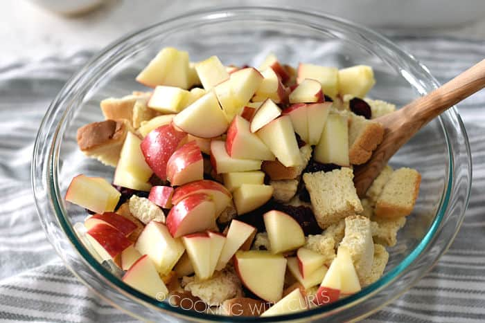 dried bread cubes, apple chunks and dried cranberries mixed together in a glass bowl with a wooden spoon.