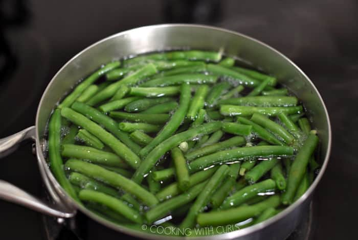 fresh green beans simmering in water in a saucepan.