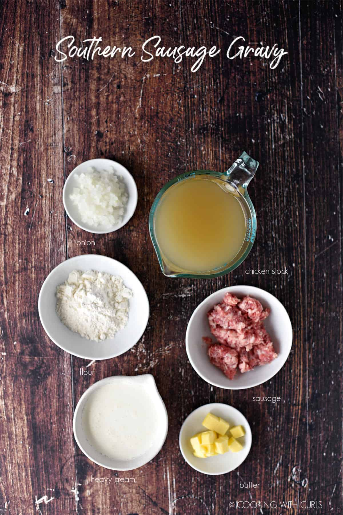 looking down on the ingredients needed to make southern sausage gravy; onion, flour, heavy cream, butter, sausage and chicken stock.