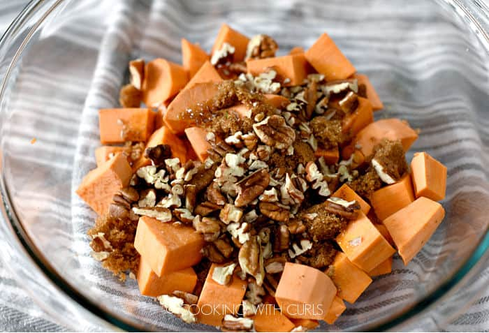 sweet yam cubes with brown sugar, spices and pecans in a clear glass bowl.
