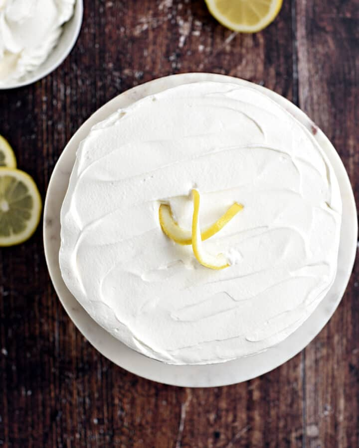 looking down on a whole lemon cheesecake topped with whipped cream, with a bowl of whipped cream and lemon slices in the background.