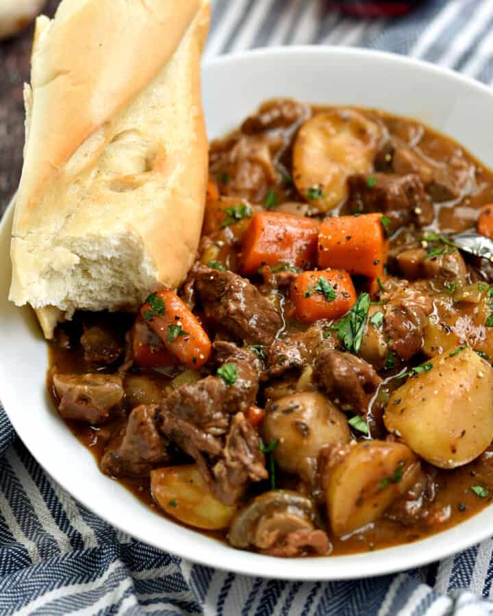 A big white bowl filled with Beef Bourguignon with a piece of baguette sitting on the side of the bowl.