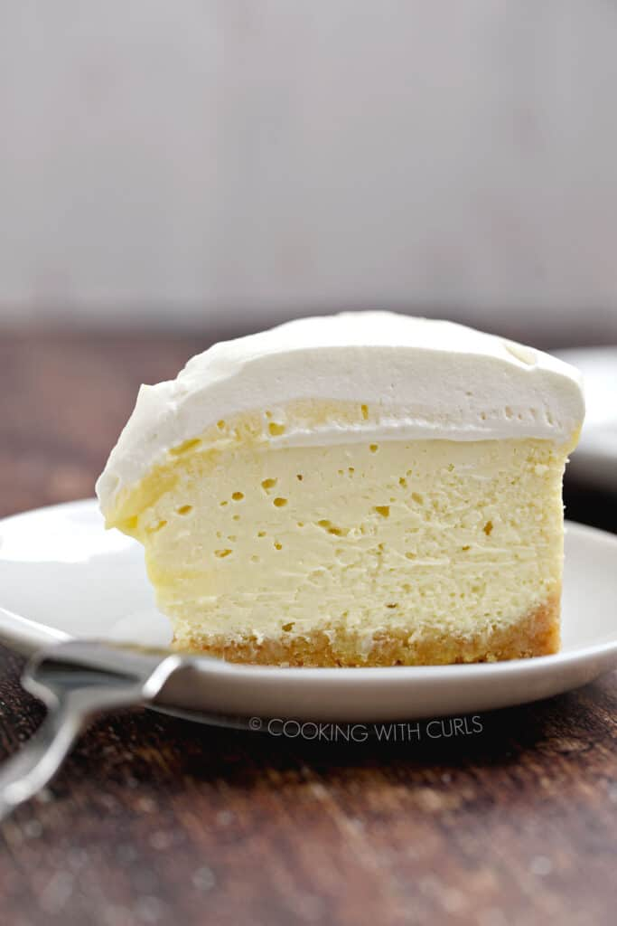 A slice of Instant Pot Lemon Cheesecake on a small white plate with a fork laying on the edge.