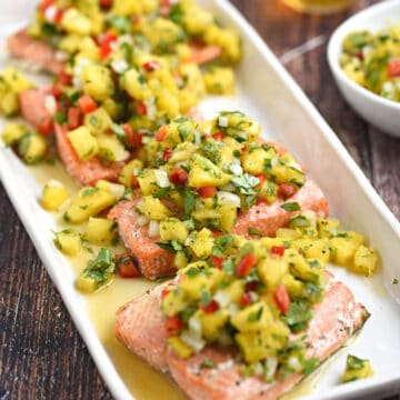 Four salmon filets topped with pineapple salsa on a white platter.