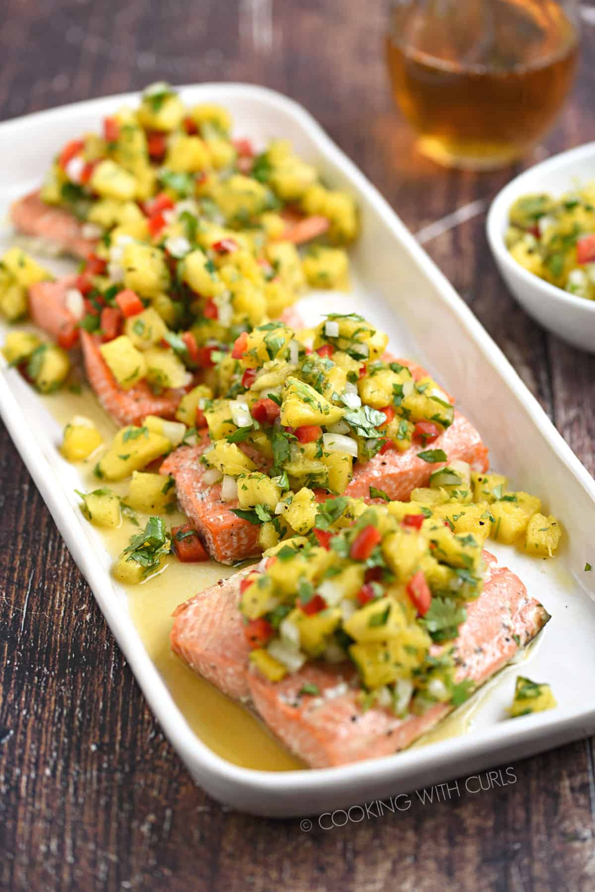 Four salmon filets topped with pineapple salsa on a white platter witha  glass of wine and bowl of salsa in the background.