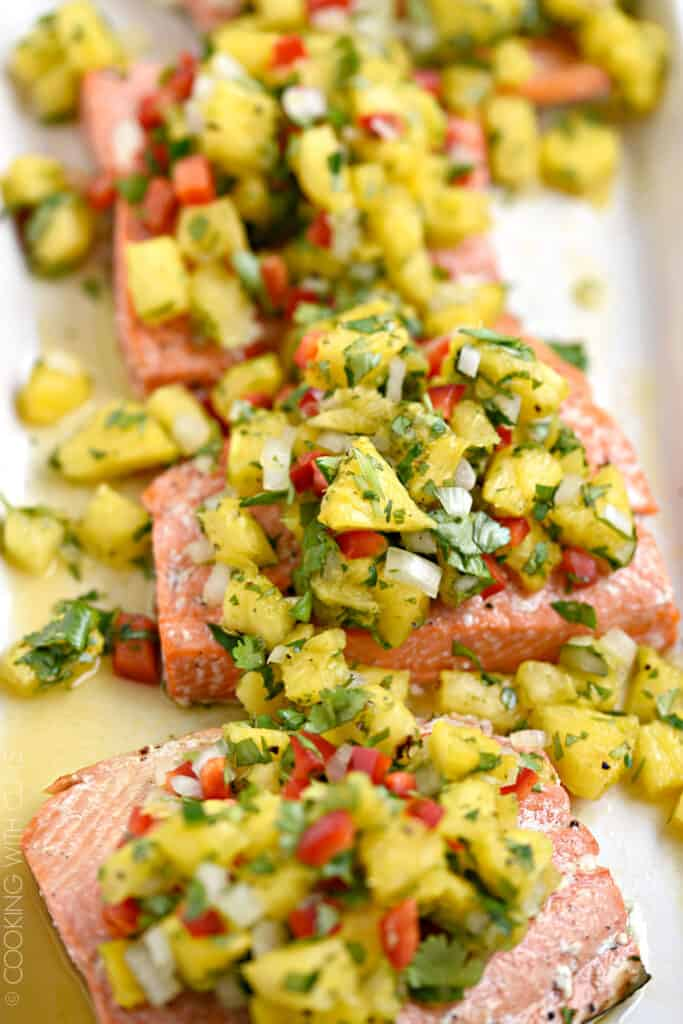 Close-up image of pineapple salsa topped salmon fillets on a white platter.
