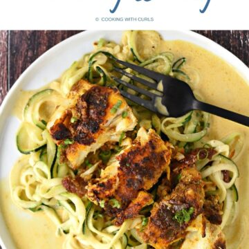 Looking down on a white plate with seasoned cod on a bed of zucchini noodle topped with a turmeric cream sauce.