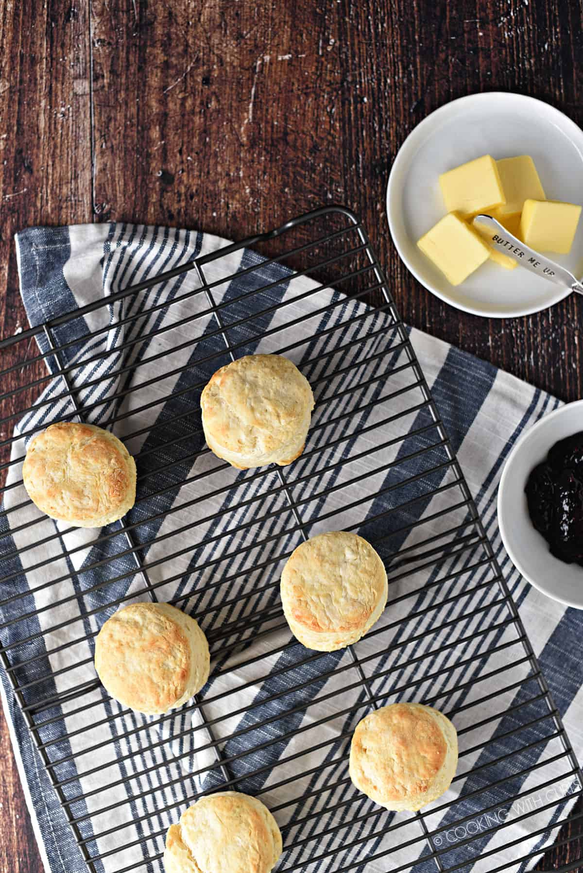 looking down on six biscuits on a black wire cooling rack laying on a blue and white striped towel with a plate of butter slices and a bowl of jam on the right hand side.