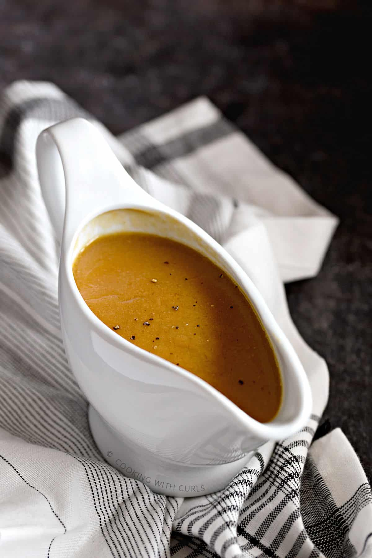 Rich, brown turkey gravy sprinkled with black pepper in a white gravy boat sitting on a black and white striped napkin.
