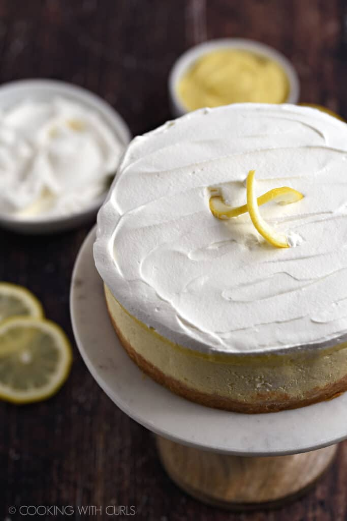 Instant Pot Lemon Cheesecake topped with lemon curd and whipped cream sitting on a marble topped cake plate with bowls of whipped cream and lemon curd in the background.