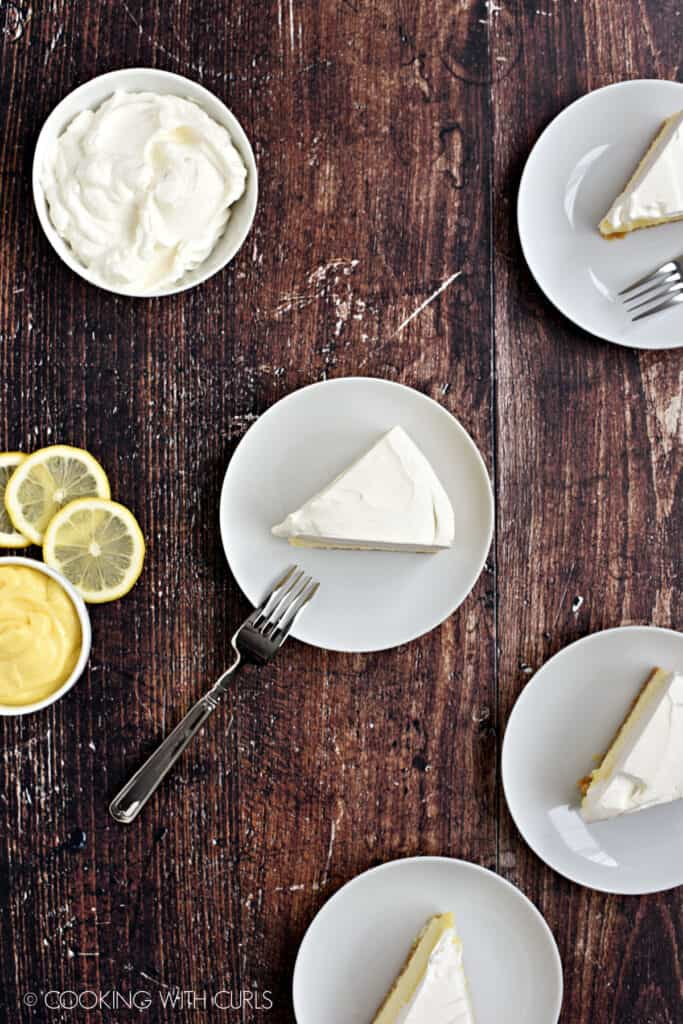 Looking down on four slices of cheesecake on small white plates, with bowls of whipped cream and lemon curd in the background.