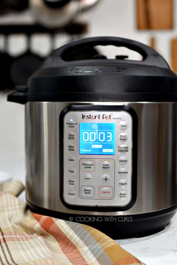 Looking straight at an Instant Pot pressure cooker with the display reading three minutes.