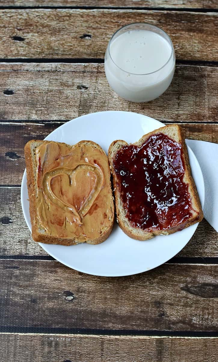 Looking down on a white plate with one slice of bread covered in peanut butter with a smear of jelly and a heart shape, and one slice of bread spread with jelly, with a glass of milk in the background.