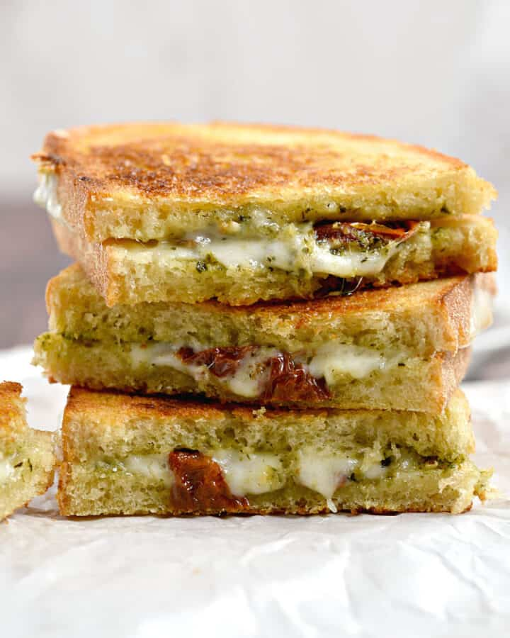 Three pesto grilled cheese halves stacked on top of each other on white parchment paper.