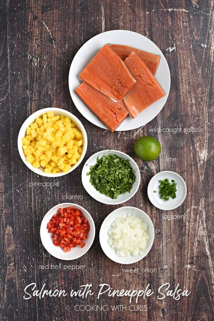 Salmon filets, chopped pineapple, red pepper, onion, jalapeno, cilantro and a lime on a wood background.