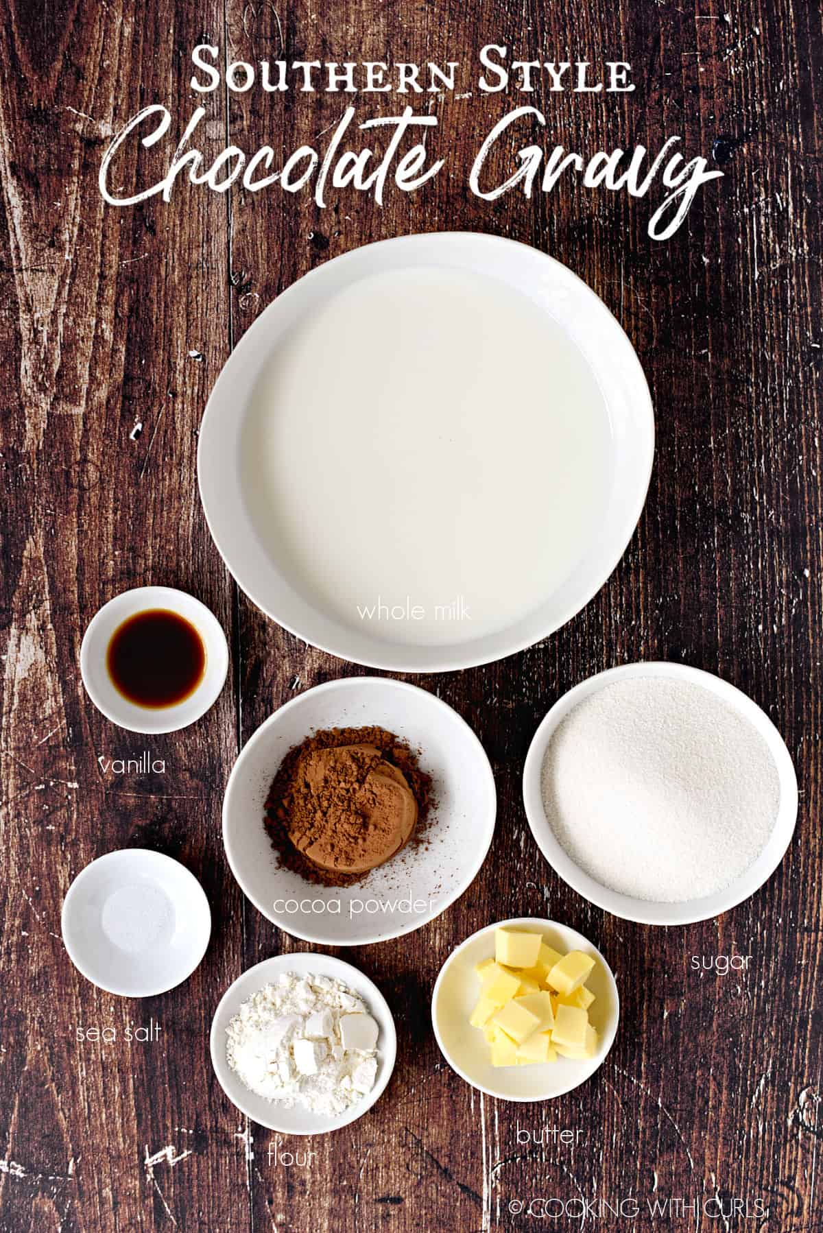 Southern Style Chocolate Gravy ingredients in white bowls; vanilla, sea salt, cocoa powder, flour, butter cubes, granulated sugar, whole milk.