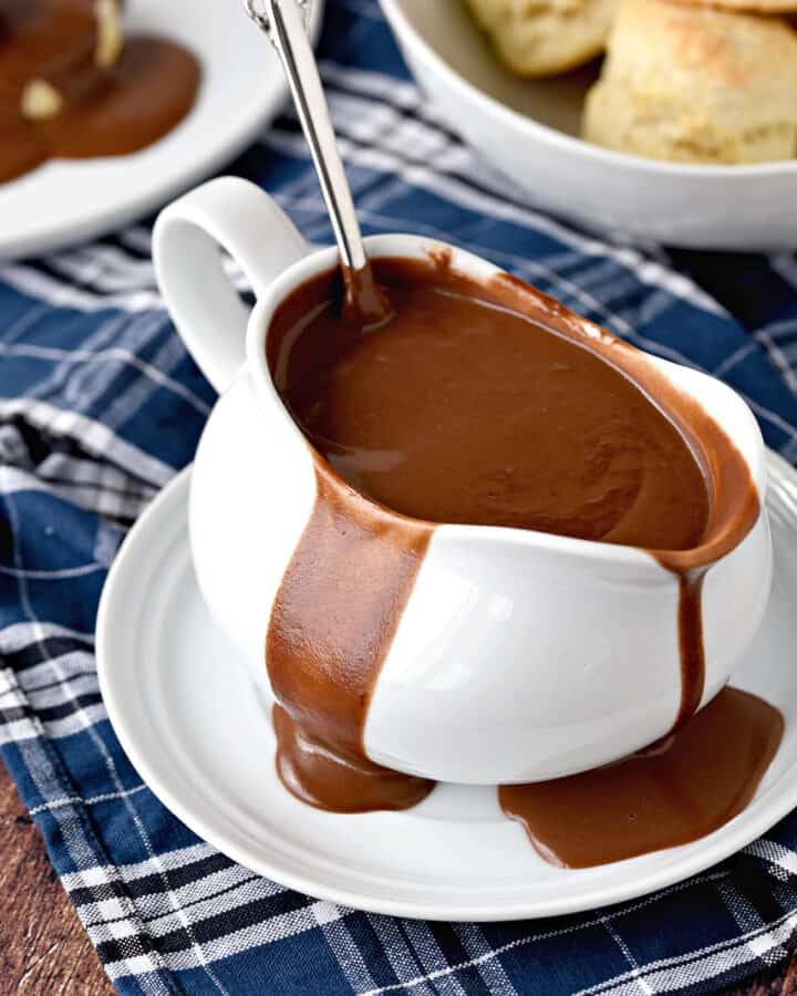 Chocolate Gravy overflowing a white gravy boat sitting on a white plate with a ladle sticking up out of the backside, with a place of chocolate gravy covered biscuits on the left and a bowl of biscuits in the upper right corner.