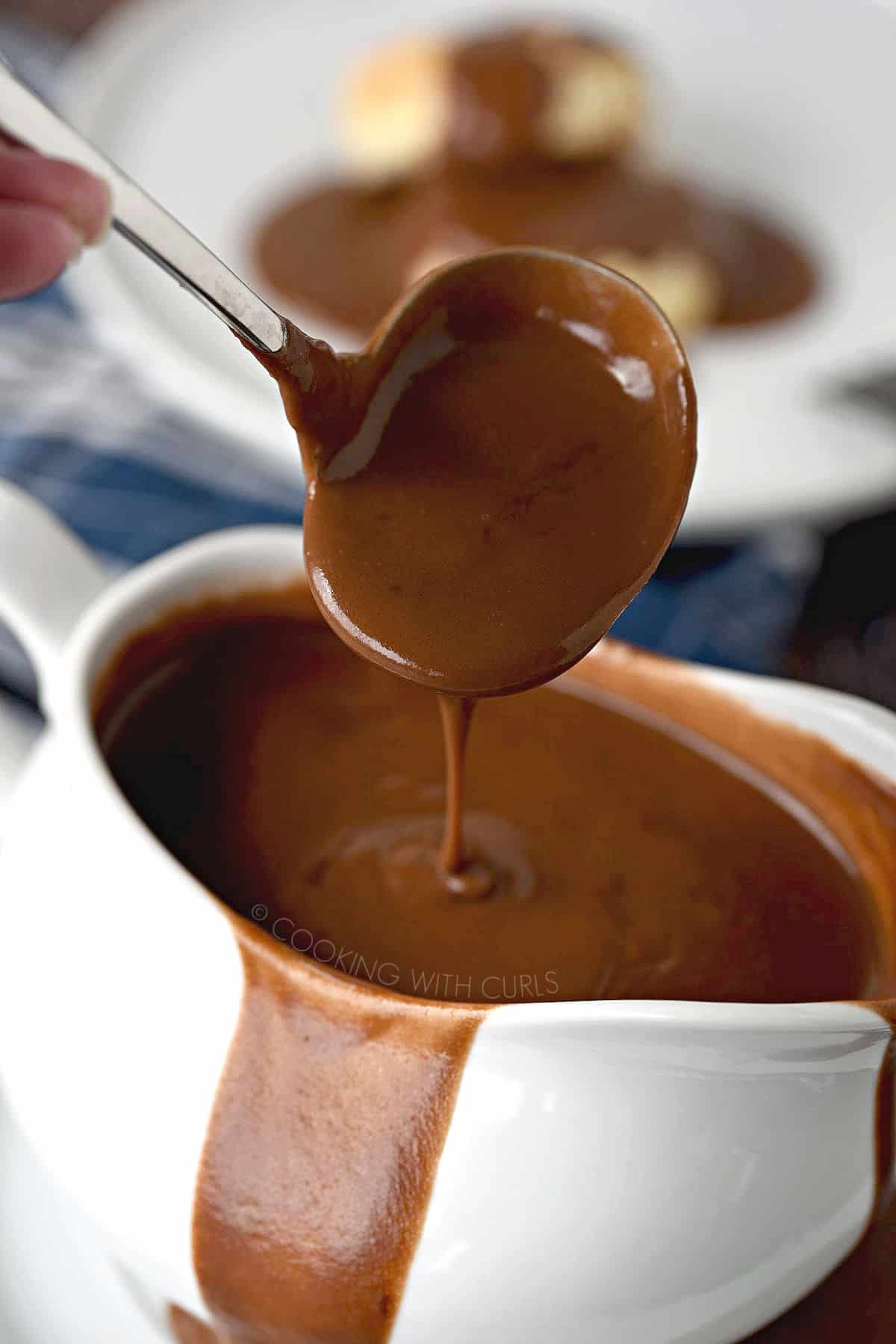 Thick, chocolate gravy dripping off the edge of a ladle into an overflowing gravy boat.