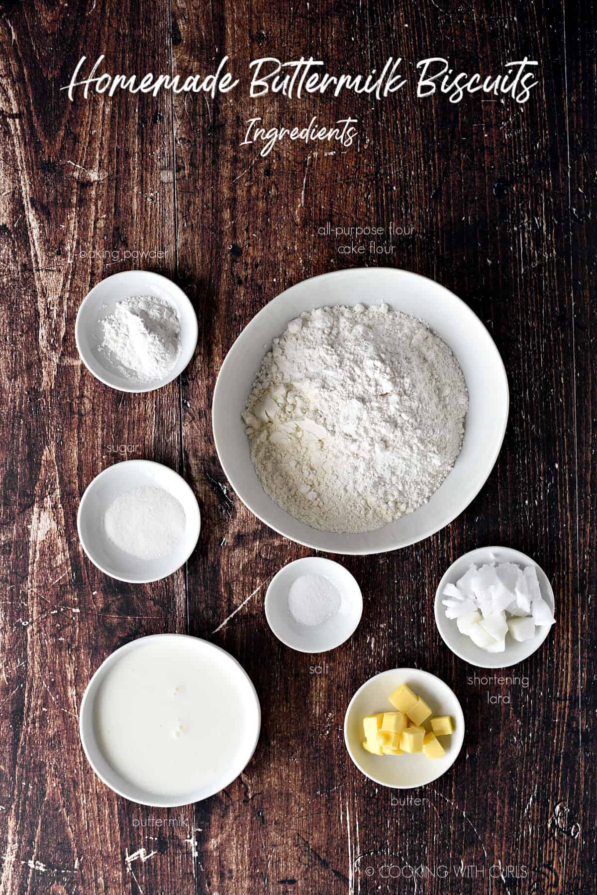 White bowls with cake and all-purpose flours, baking powder, sugar, salt, buttermilk, butter, shortening and lard.