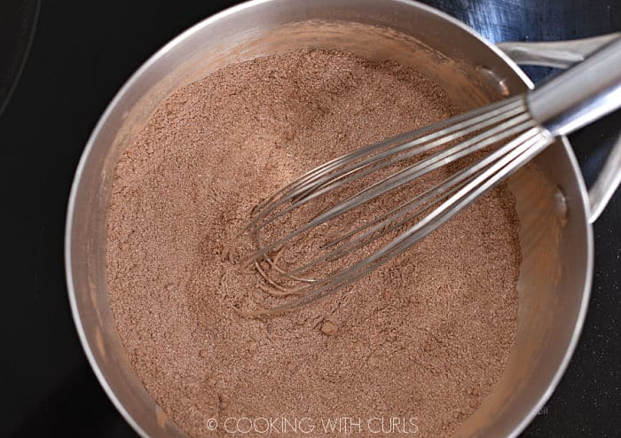 looking down on cocoa powder, flour, salt and sugar mixed together with a wire whisk in a saucepan.