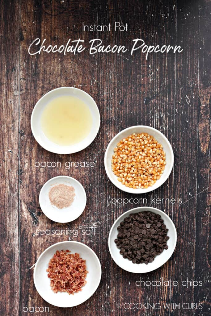 Bacon grease, popcorn kernels, seasoning salt, chocolate chips and bacon in small white bowls on a wooden background.
