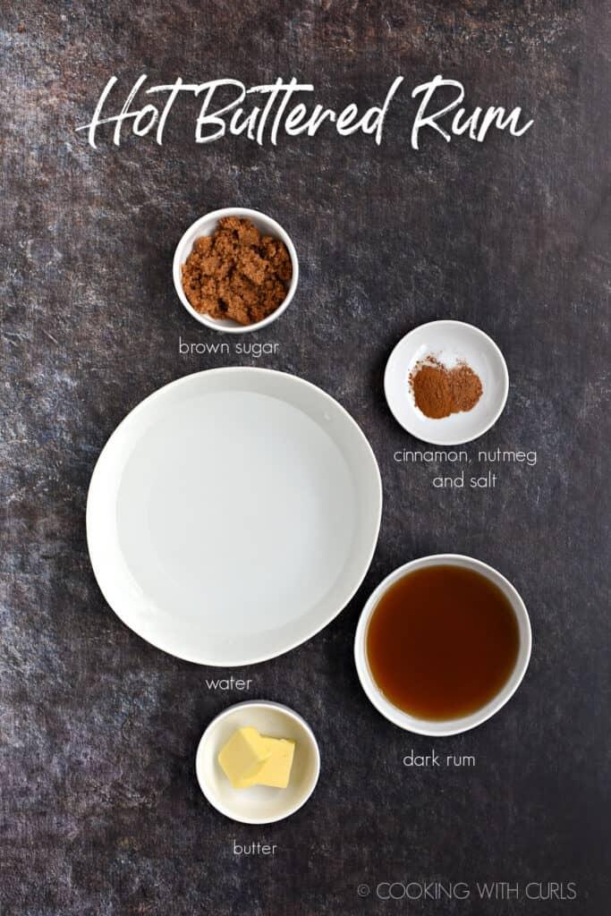 Brown sugar, cinnamon, nutmeg, salt, water, butter and dark rum in white bowls.
