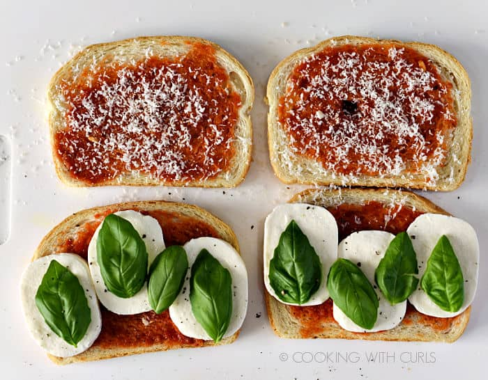 Eight fresh basil leaves laying on the mozzarella cheese slices.