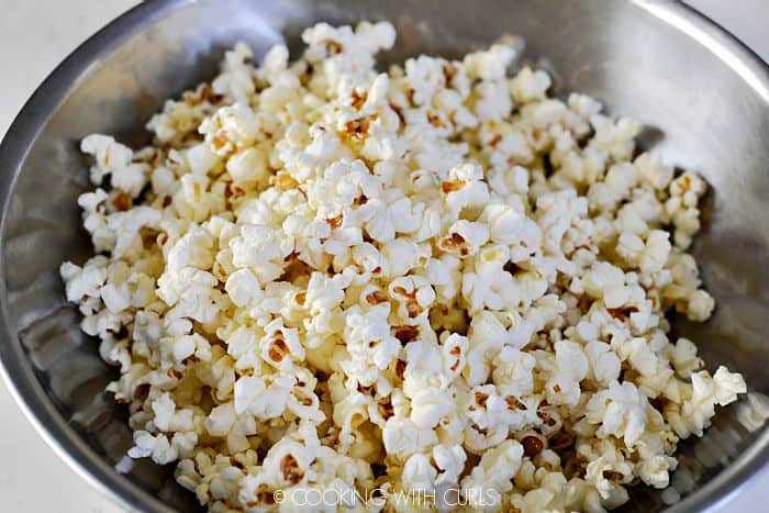 Freshly popped popcorn in a stainless steel bowl.