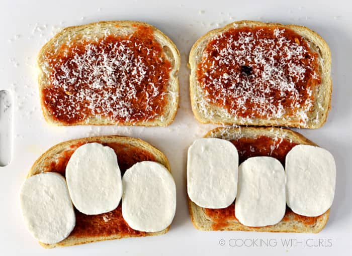 Grated Parmesan cheese sprinkled over two slices of sauce covered bread and six slices of mozzarella cheese arranged over two slices of sauce covered bread.