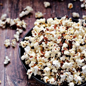 Instant Pot Chocolate Bacon Popcorn in a dark blue bowl falling out on a wooden background
