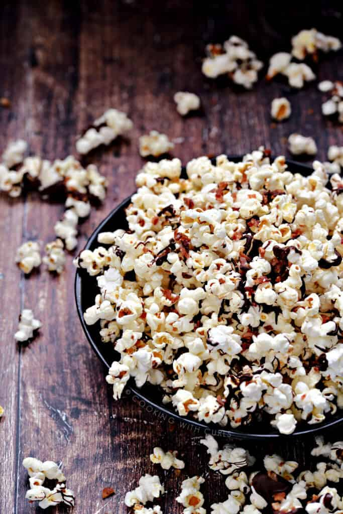 Instant Pot Chocolate and Bacon Popcorn overflowing a dark blue bowl onto a wooden surface.