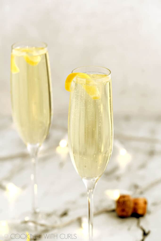 Two champagne flutes fill with limoncello prosecco spritzer and a lemon twist surrounded by small lights.