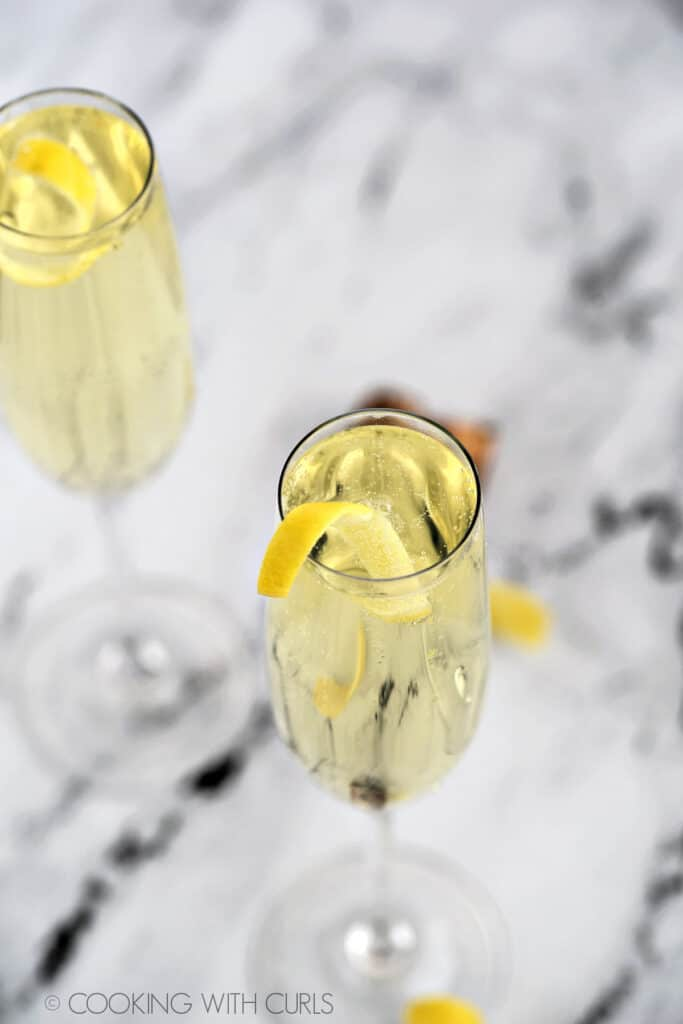 Looking down on two champagne flutes filled with limoncello spritzer with a lemon twist.