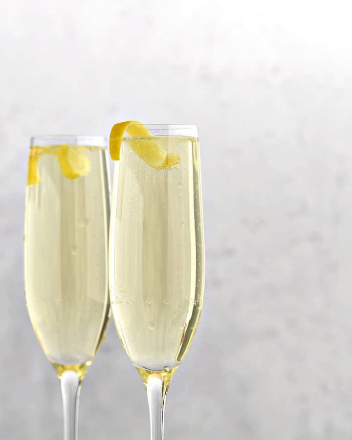 Two champagne flutes filled with Limoncello Spritzer with Prosecco and a lemon twist.