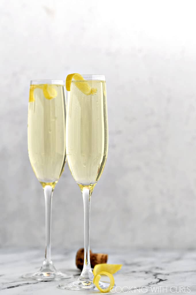 Two champagne flutes filled with limoncello, prosecco and club soda with a lemon twist.